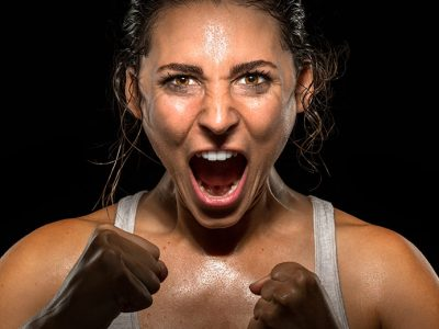Sports woman screaming with fists clenched, determined to succeed