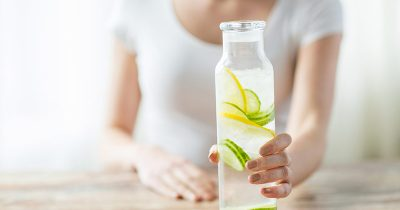 Close up of woman with fruit water in glass bottle