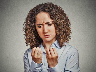 Woman with OCD looking at nails