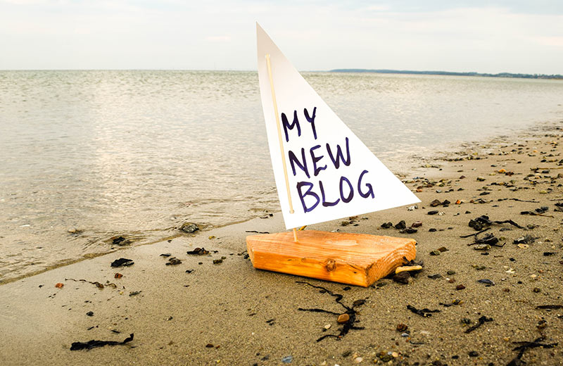 Starting a Blog - A small wooden boat ready to set sail on a beach at the the edge of the sea, with the words 'My New Blog' written on the sail