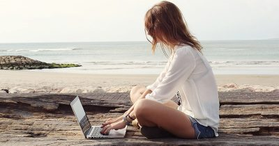 You woman who is becoming a freelance writer, working on her laptop at the beach