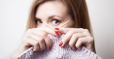 Woman with her own knitting business looks through a gap in her knitting needles