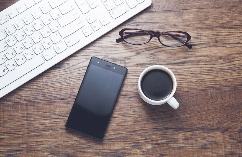 Writing apps being used on smart phone next to keyboard, coffee and glasses on a desk