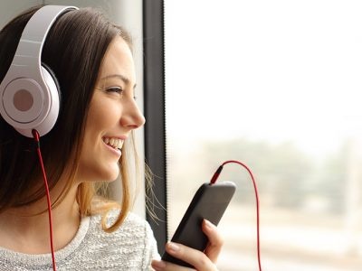 Smiling woman on the train listening to business podcasts on her smart phone