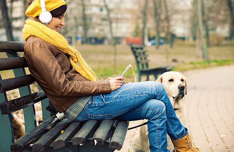 Woman listening to a dog podcast in the park as she walks her dog