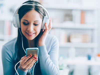 Woman listening to mental health podcasts on a handheld audio device