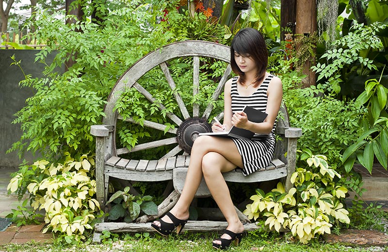 Woman at a writers retreat working on a bench in a garden