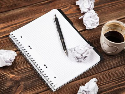 Desk of someone with creative block - papers crumpled up, blank page