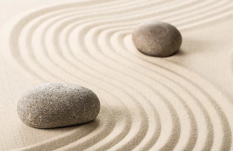 Feng Shui concept photograph of a round stone with sand raked around it