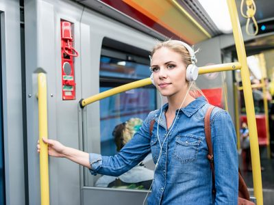Woman using her commute to listen to study materials