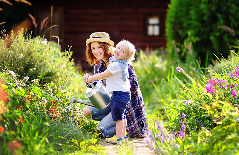 Mother and child using homemade weed killer in garden