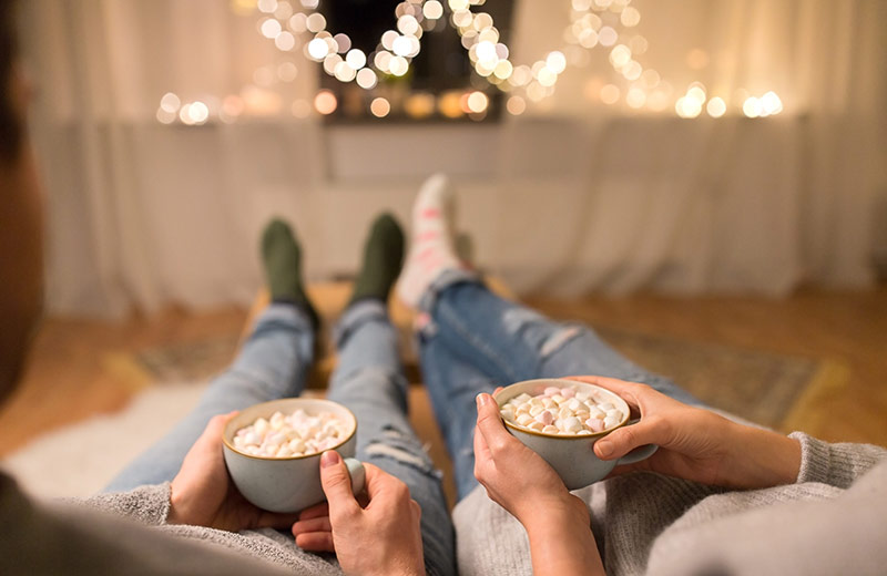 Couple with hot chocolate and marshmallows, feeling Christmassy