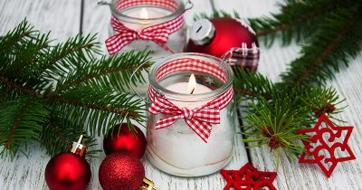 Christmas candles amongst Christmas tree decorations and a festive wreath