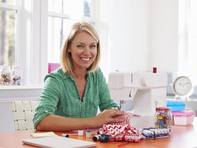 Happy woman crafting something with her sewing machine