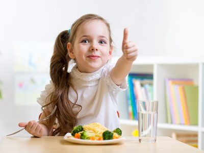 Child eating a healthy meal and giving it the thumbs up
