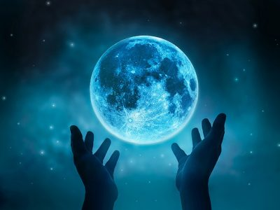 Pair of hands reaching up to a full Moon as they perform Moon magic