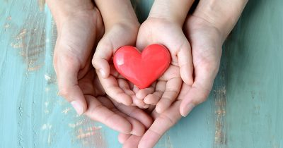 A mother's hands enclosed around a child's hands, which are holding a heart