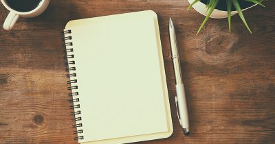 Top-down view of an open notebook on a wooden table - ready for journalling. Next to it are a cup of coffee and a cactus.
