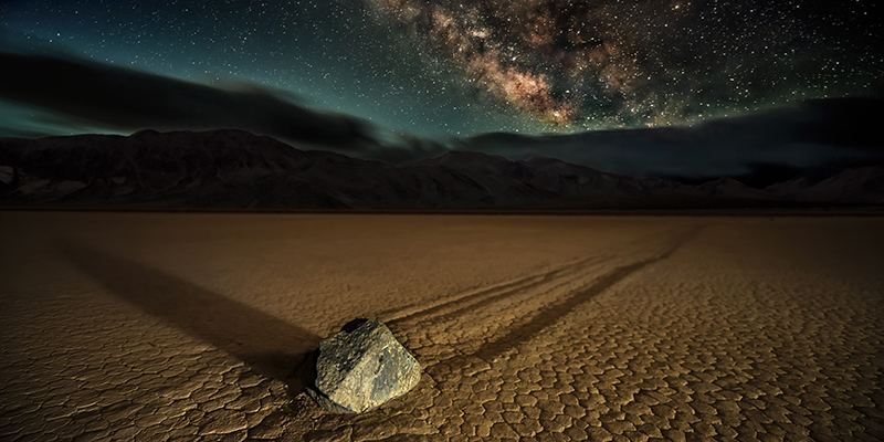 Racetrack Playa. A 'Sailing Stone' photographed at night under the Milky Way at California's Death Valley National Park at the Racetrack Playa