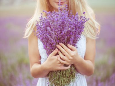 A woman in a field holding a crop of herbs and demonstrating how to care for lavender