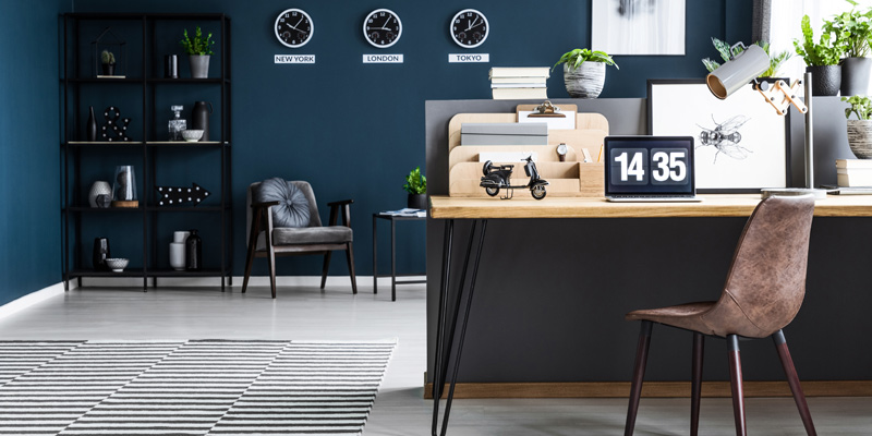 A royal blue home office with dark seating and global clock hanging on the navy walls.