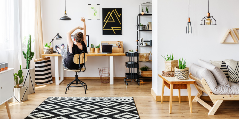 A young woman stretching and taking a break from work in her trendy home office.