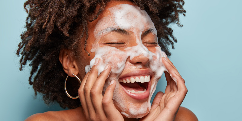 A smiling woman washing her face to take care of her skin anatomy