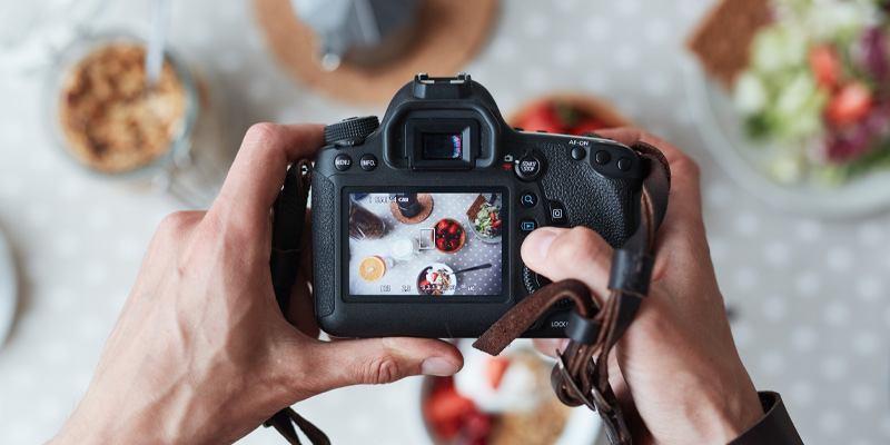 Photographer using a DSLR from a photography starter kit to take food pictures