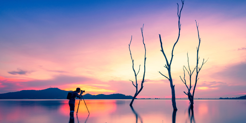 Photographer using a tripod from a photography starter kit to take low light images at sunset