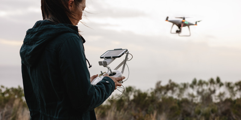 Photographer using a drone from a photography starter kit to take aerial images