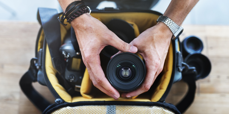 Photographer packing his photography starter kit into a camera bag
