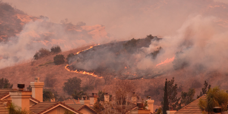 A wildfire by some houses illustrating the climate changing
