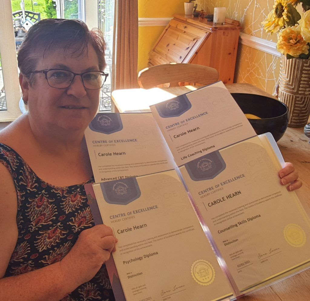 Carole Hearn with her Centre of Excellence diplomas after studying CBT for depression.