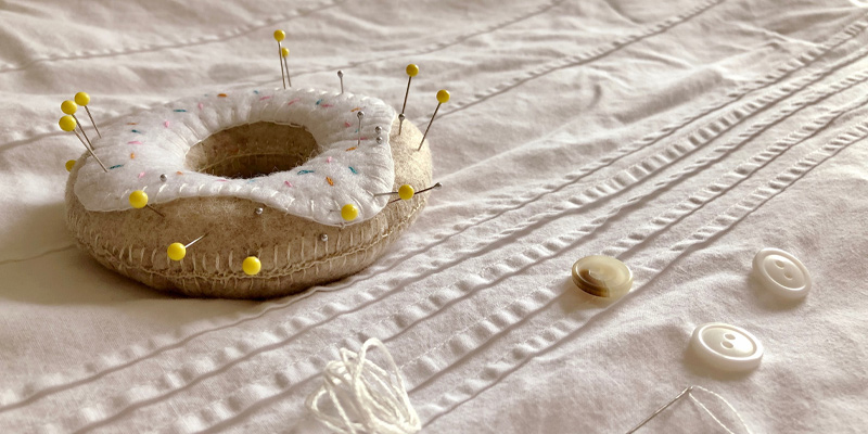 A [pin cushion in the shape of a donut beginners can learn how to sew.
