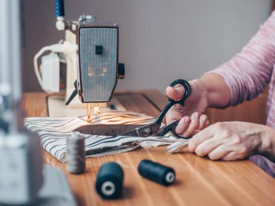 A woman learning how to sew cutting fabric at her sewing kit.