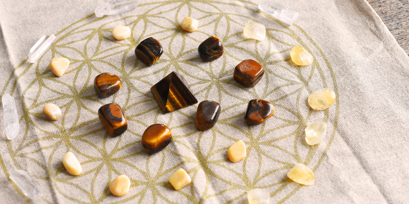 A close up image of a crystal prosperity grid using clear quartz, tiger's eye and citrine crystals.