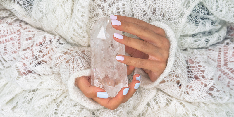 Woman's hands holding the clear quartz natural protection crystal.