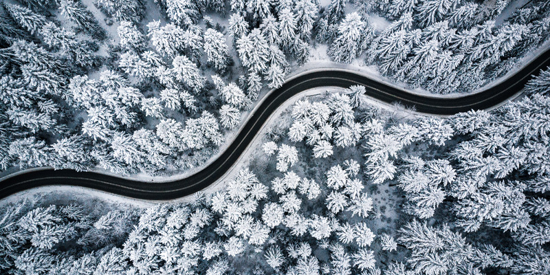 Top down aerial view of a curvy windy road in snow covered example of one of the forest biomes.
