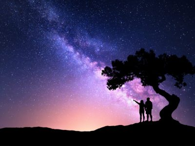 A couple stand under a tree and look up into the night sky at the Milky Way galaxy.