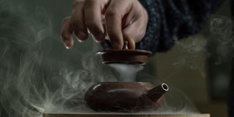 A man opening a teapot in which you can make ginger tea.