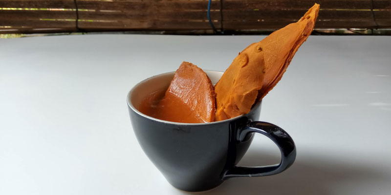 A picture of java ginger used to make ginger tea in a black mug.