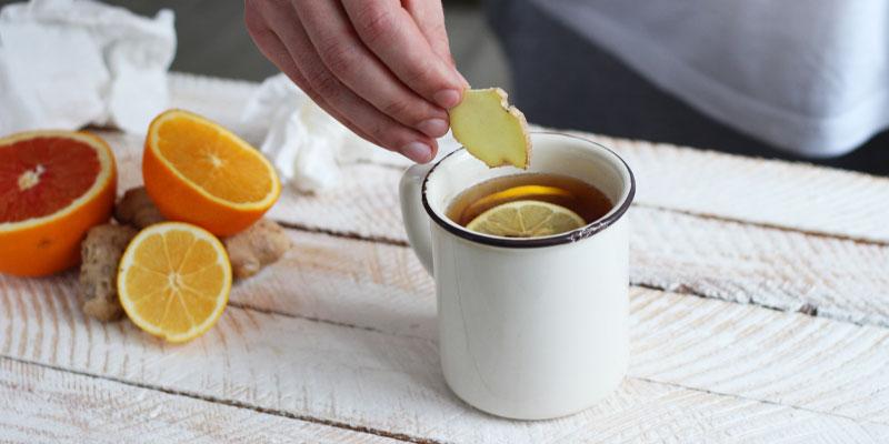 A man holding sliced ginger used to make ginger tea in white mug.