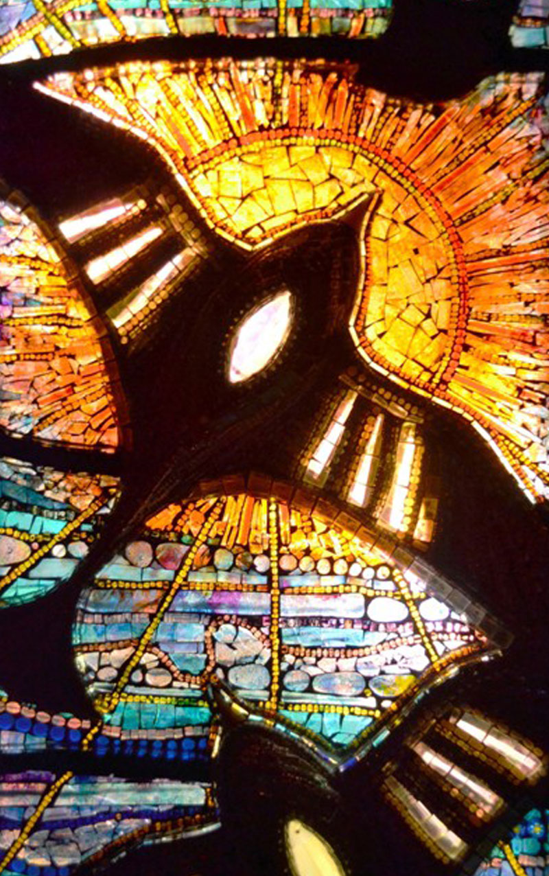 A natural stained glass work using sacred geometry depicting a bird in the sky.